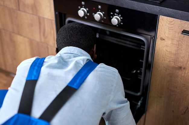 Tuttofare africano esaminando il forno elettrico in cucina a casa. riparazione di elettrodomestici. vista posteriore sul maschio afroamericano in tuta blu concentrato sul lavoro, la riparazione, il duro lavoro professionale qualificato