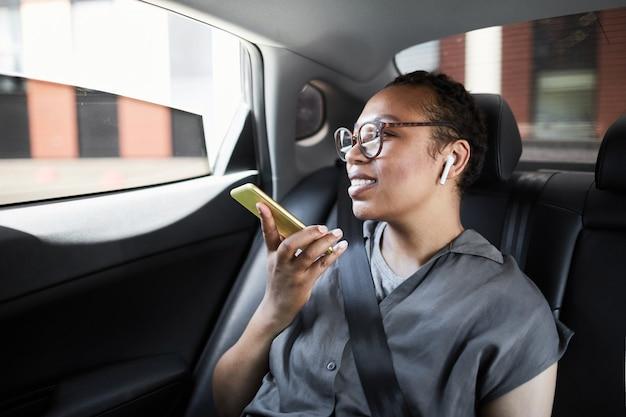Donna africana felice seduta sul sedile posteriore dell'auto che parla al cellulare e sorride