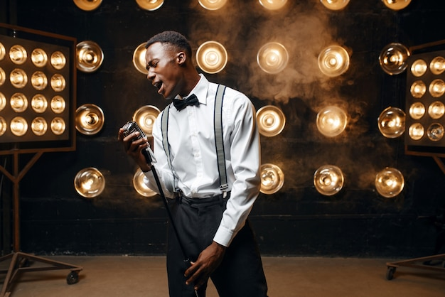 Esecutore di jazz africano che canta sul palco. jazzman nero che si esibisce sulla scena con i riflettori