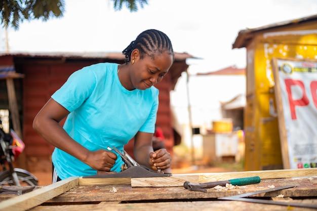 Signora africana che usa la pialla per vestire il legno in taglia