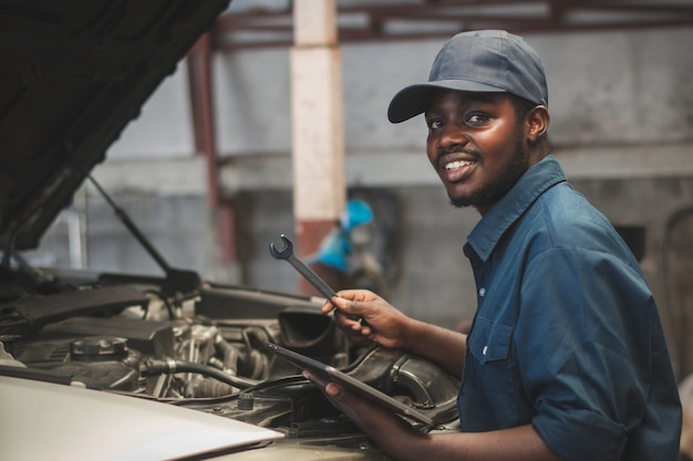 Manutenzione maschile africana che controlla l'auto con chiave inglese e tablet, servizio tramite sistema assicurativo presso il centro di riparazione e controllo auomobile