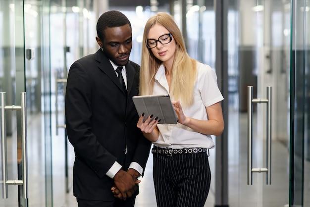 Impiegati di concetto maschii e caucasici femminili africani con il pc della compressa che sta al corridoio di ufficio vuoto e che discute nuovo progetto.