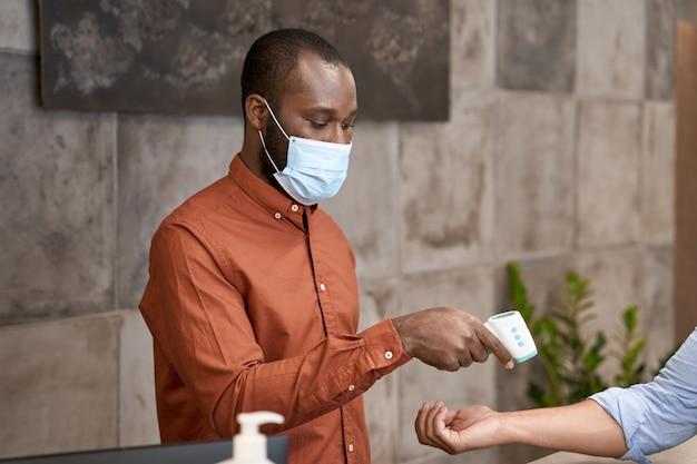 Receptionist maschio africano che indossa una maschera medica utilizzando un termometro a infrarossi per misurare il corpo