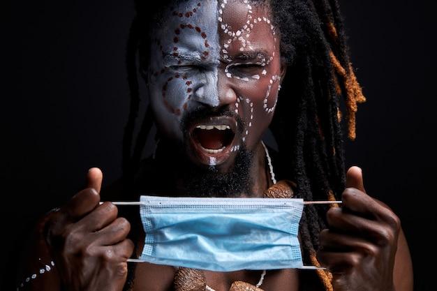 Il maschio africano urla dal dolore, indosserà una maschera medica sul viso, sta con la bocca aperta. muro nero isolato