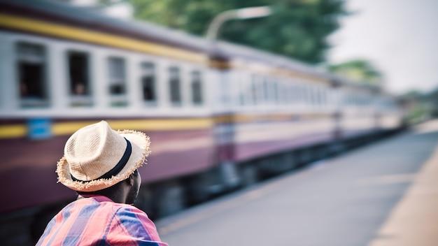 Il turista maschio africano si siede da solo in attesa di un treno su un treno sulla piattaforma della stazione ferroviaria