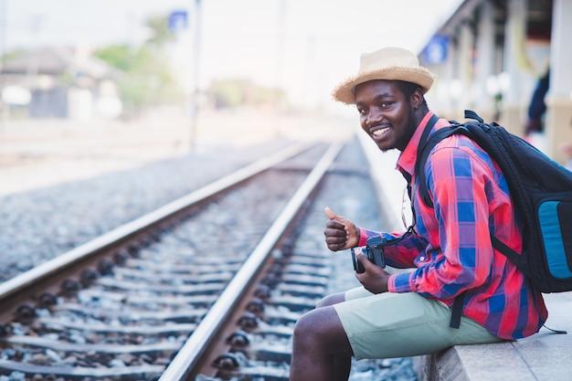 Viaggiatore maschio africano che aspetta il treno sulla stazione ferroviaria. concetto di viaggio avventuroso