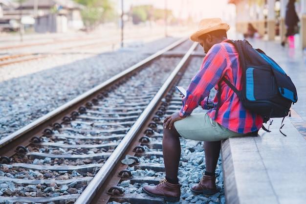 Viaggiatore maschio africano in attesa del treno sulla stazione ferroviaria con l'utilizzo di smartphone. concetto di viaggio avventuroso