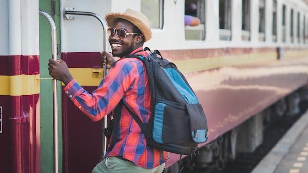 Viaggiatore maschio africano con cappello e zaino traino al treno sulla stazione ferroviaria. concetto di viaggio avventuroso