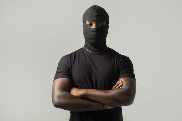 Uomo africano in una maschera nera e una maglietta nera su un muro grigio