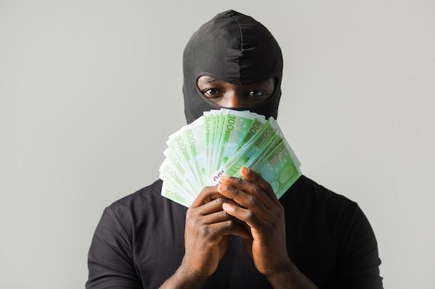 Uomo africano in una maschera da ladro nero e in una maglietta nera su un muro grigio con euro in mano