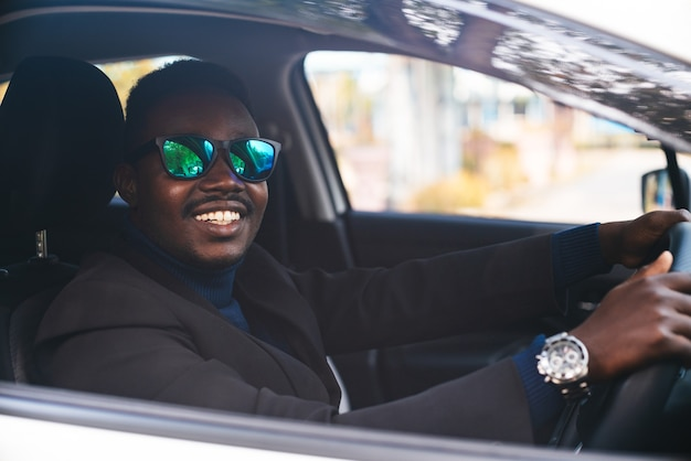 L'uomo africano in un abito nero seduto al volante con un sorriso e felice