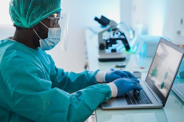 Medico africano dell'uomo che lavora con il computer portatile all'interno dell'ospedale del laboratorio - fuoco sulla mano destra
