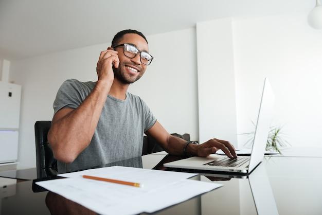 Uomo africano vestito con una t-shirt grigia e con gli occhiali che parla al cellulare mentre usa il laptop.