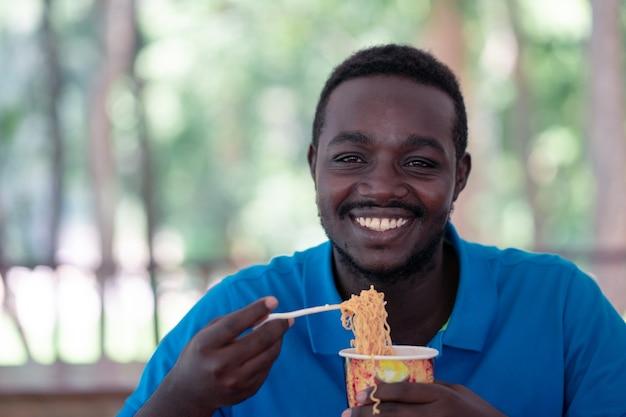 Uomo africano che mangia zuppa di noodle istantanea