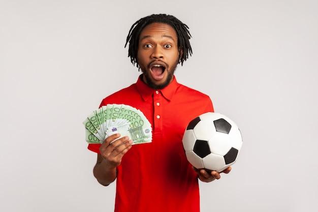 Uomo africano che tiene banconote in euro e pallone da calcio, scommette sullo sport, vittoria.