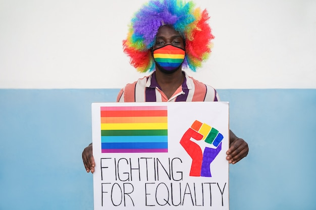 Uomo africano che tiene la bandiera lgbt alla dimostrazione del gay pride mentre indossa la maschera di sicurezza arcobaleno