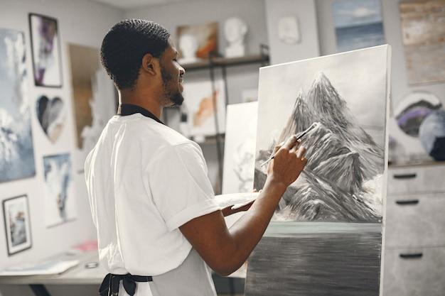 L'uomo africano nella classe di pittura disegno su un cavalletto.