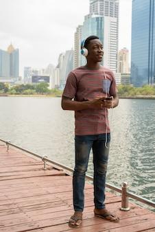 Uomo africano nel parco utilizzando il telefono cellulare e ascoltare musica con le cuffie