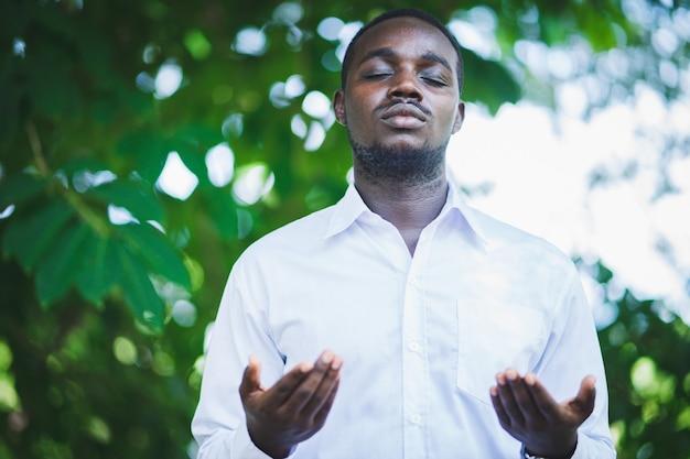 Uomo africano che prega per ringraziare dio nella natura verde