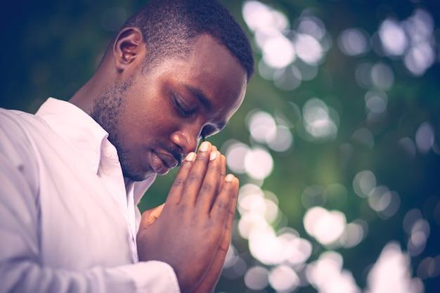 Uomo africano che prega per grazie a dio.