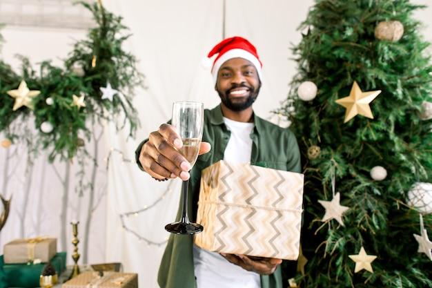 Uomo africano in cappello della santa vicino all'albero di natale che tiene champagne e regalo presente