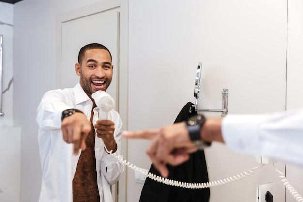 L'uomo africano in camicia canta con l'asciugacapelli in mano e indica lo specchio in bagno