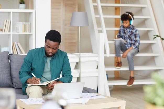Uomo africano seduto sul divano e lavora online con documenti e laptop