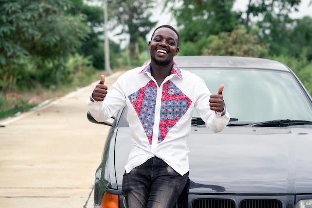 Uomo africano che sorride mentre sedendosi sulla parte anteriore di un'automobile