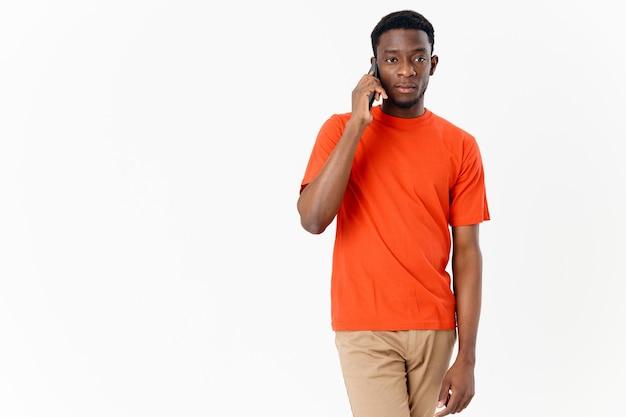 Uomo africano che parla al telefono su uno sfondo chiaro