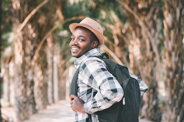 Viaggiatore africano dell'uomo che trasporta zaino che cammina attraverso il parco