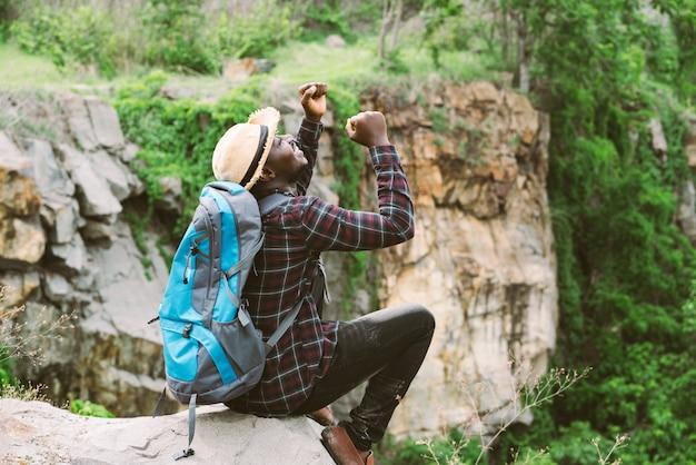 Viaggiatore africano dell'uomo che si siede sulla scogliera e che tiene macchina fotografica con lo zaino