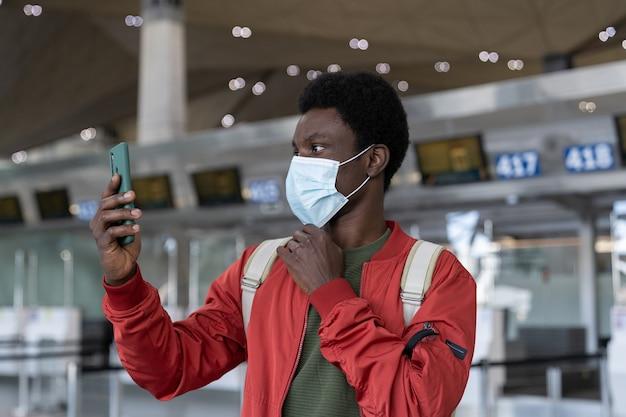 Uomo africano che utilizza la funzione id viso su smartphone in maschera medica in aeroporto in quarantena covid
