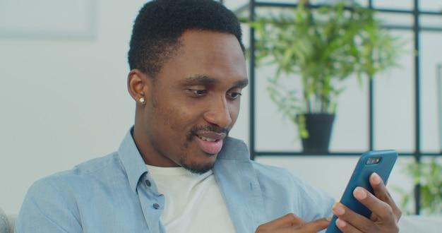 Uomo africano utilizzando il telefono cellulare sul divano a casa uomo che trova buone notizie su smart phone seduto su un divano a casa