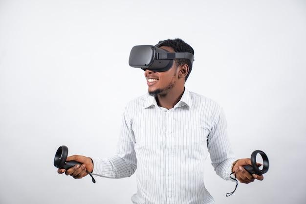 Uomo africano che usa un auricolare vr e tiene in mano i controller per i giochi
