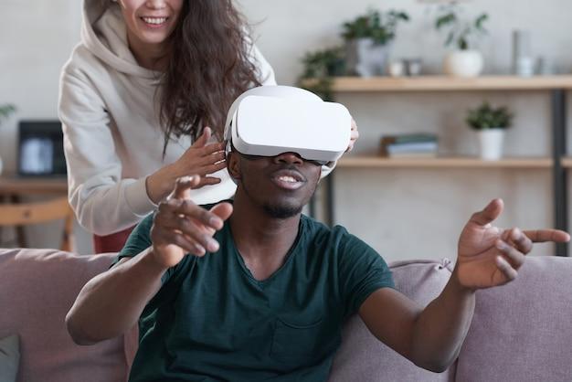 Uomo africano con gli occhiali vr che gesticola mentre guarda un film di realtà virtuale con una donna sullo sfondo