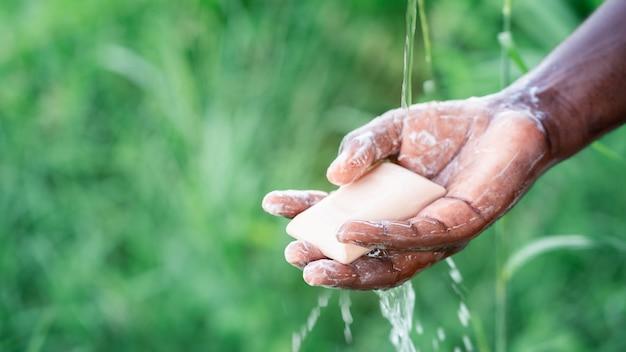 Mani di lavaggio uomo africano con sapone