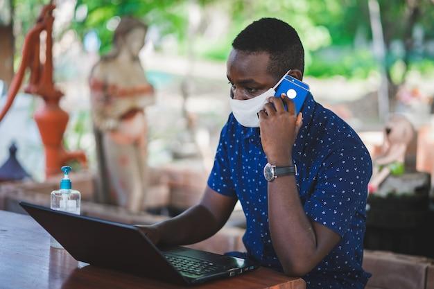 Uomo africano che indossa una maschera e utilizza un computer portatile a casa. whf o il concetto di lavoro da casa