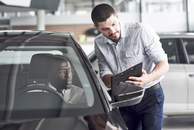 Un uomo africano che acquista una macchina nuova controlla un'auto parlando con un venditore professionista.