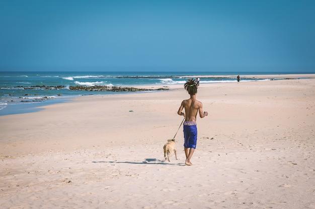 Uomo africano con i capelli dei dreadlocks che corre con il suo cane sulla spiaggia di jeffreys bay, sudafrica