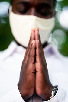 Uomo africano con maschera facciale che prega per combattere l'epidemia di coronavirus