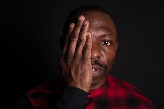 Uomo africano con la mano sul viso fermare il razzismo