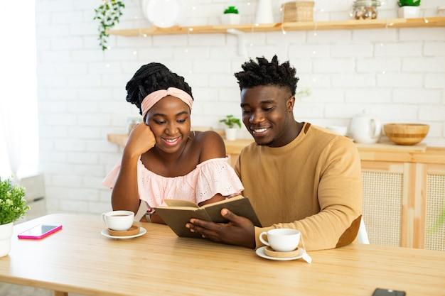 Uomo africano e donna in cucina leggendo un libro insieme