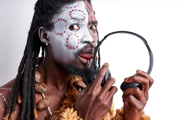 L'uomo nativo africano assaggia le cuffie, le lecca, le usa in modo errato. maschio in abbigliamento etnico aborigeno isolato sul muro bianco