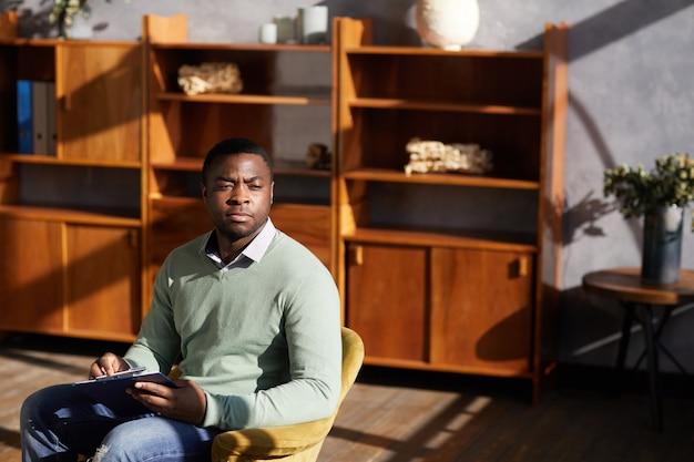 Uomo pensieroso africano con documento pensando ai suoi piani futuri mentre è seduto su una sedia in ufficio