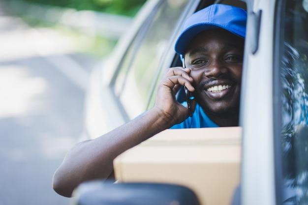 Uomo di corriere consegna postale africano utilizzando smart phone e consegna pacchetto in auto