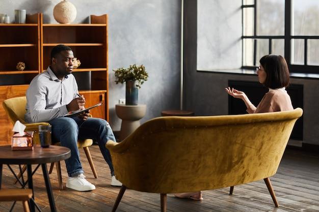 Psicologo africano seduto su una sedia e parlando con la giovane donna che discutono di alcuni problemi durante la terapia psicologica