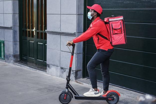 Cavaliere africano che consegna un pasto con uno scooter elettrico - focus on face