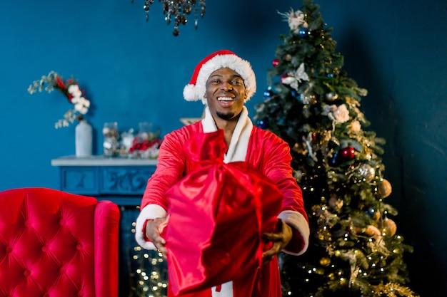 Babbo natale africano sta davanti all'albero di natale, con in mano un sacco con i regali