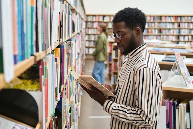 Studente africano in piedi davanti agli scaffali e legge un libro in biblioteca