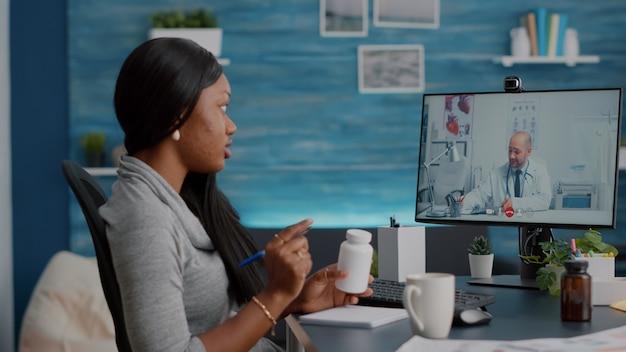 Studente africano che parla con un medico che spiega i sintomi della malattia discutendo il trattamento delle pillole